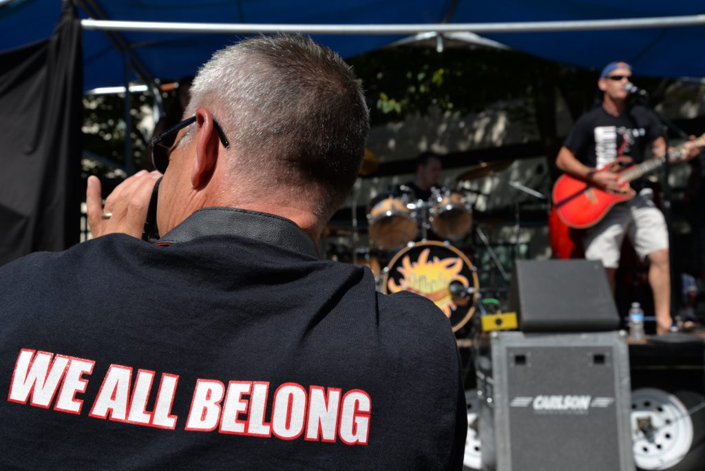 Outdoor festival, band playing in background. Forergound image of the back of a man wearing a t-shirt with the words We All Belong.