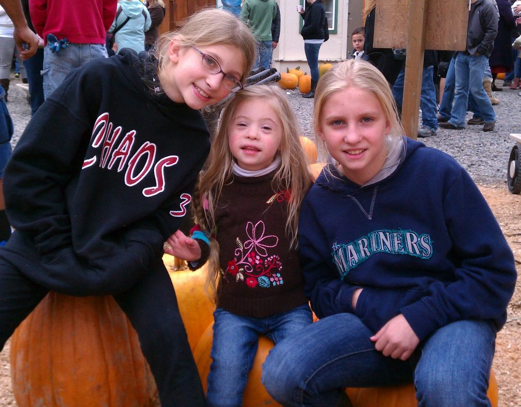 Three sisters sitting on giant pumpkins.