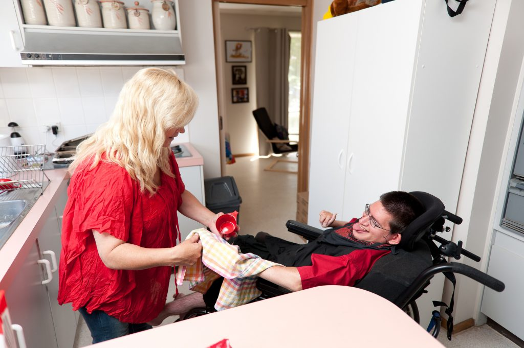Woman helping a man in wheelchair dry dishes.