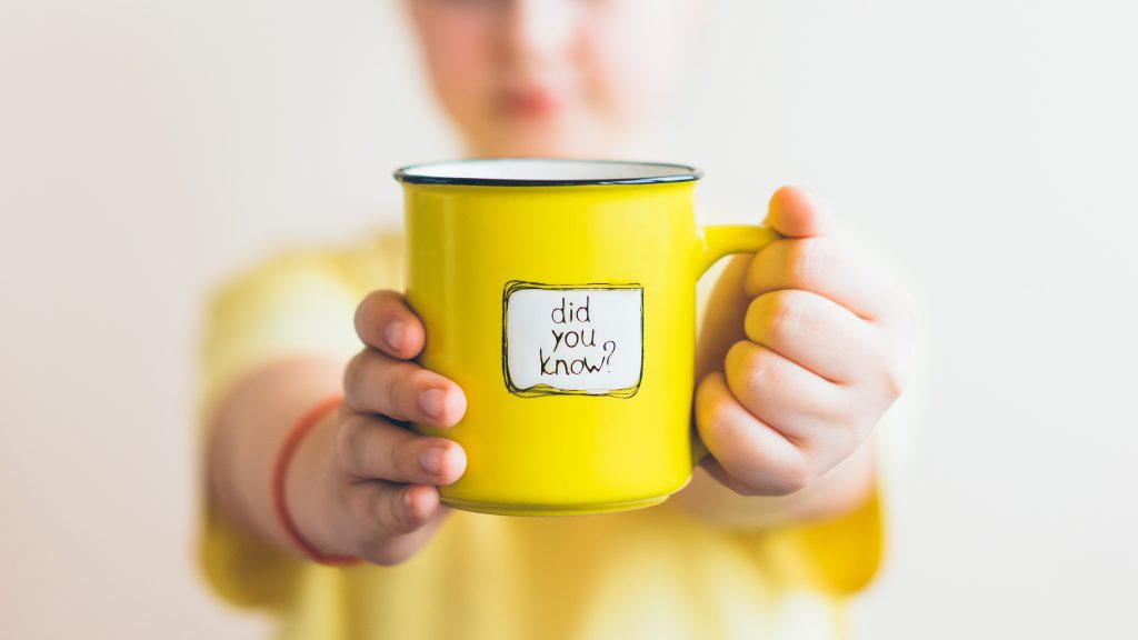 A girl in a yellow T-shirt with a yellow cup in her hand, on which was written Did you know. Interesting fact.