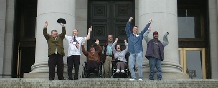 Disability advocates cheering on steps of state capitol building in Olympia, WA.