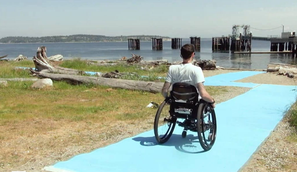 Man in wheelchair on accessbile beach trail next to Puget Sound waters..