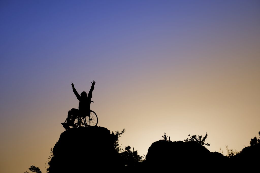 Silhouette of girl in a wheelchair on a rock outcropping, arms reaching toward the sky.