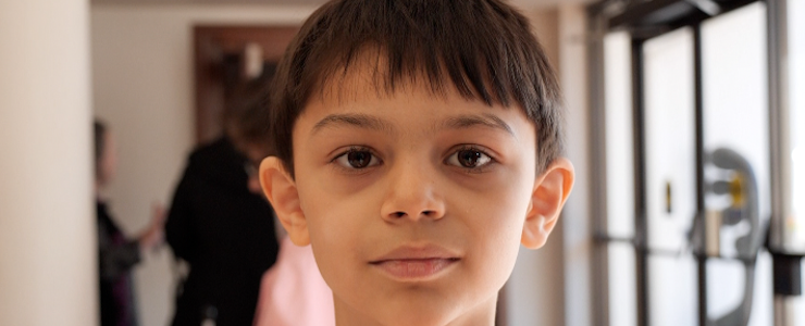 Young boy looking into camera. Blurry background.