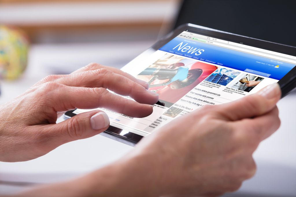 Close-up Of A Person's Hand Using Digital Tablet With Screen Showing Online News