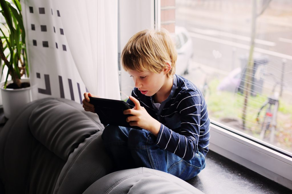 7 year old boy sitting near the window and playing tablet
