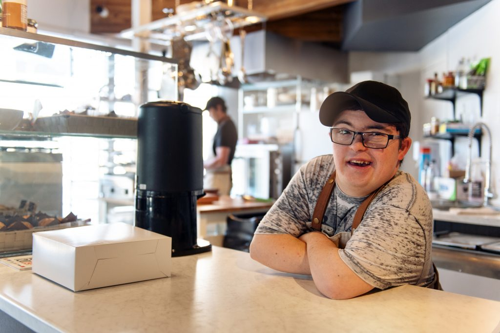 A man with Down syndrome working at the counter of a coffee shop.
