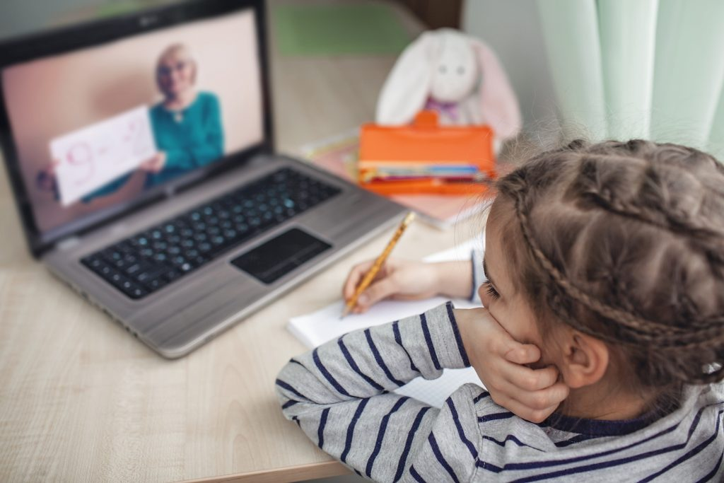 schoolgirl studying homework math during her online lesson at home, social distance during quarantine, self-isolation, online education concept.