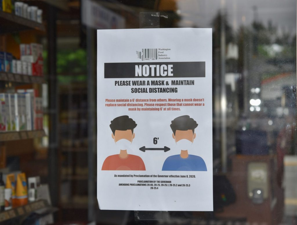 Notice of face covering ordinance in the window of a pharmacy.