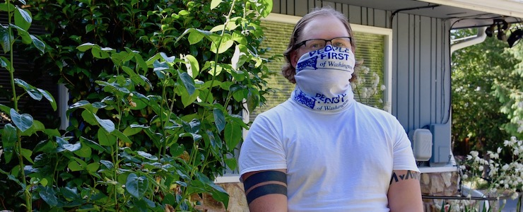 Man wearing People First gaiter, standing in front of house.