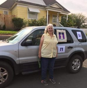 Debbie Chapman stands beside her car with Informing Families logos outside a car parade in Ritzville WA.