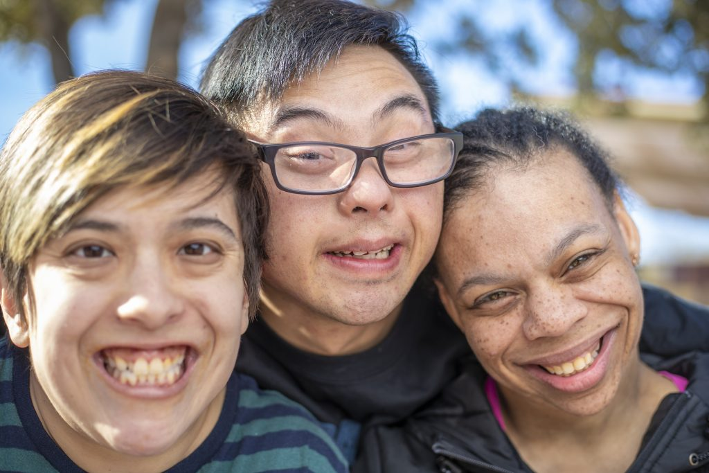 A group of friends with intellectual disabilities living a vibrant and happy life.