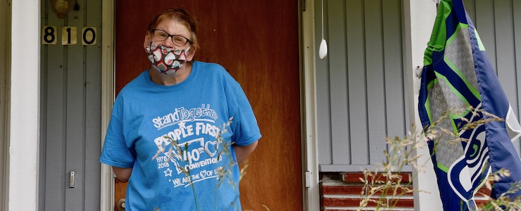 Disabled woman with People First t-shirt wearing a mask, standing outside on a porch.