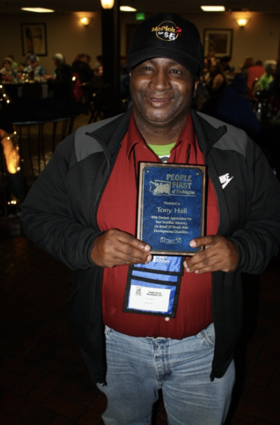 Tony Hall holding a plaque of appreciation from People First of Washington State.
