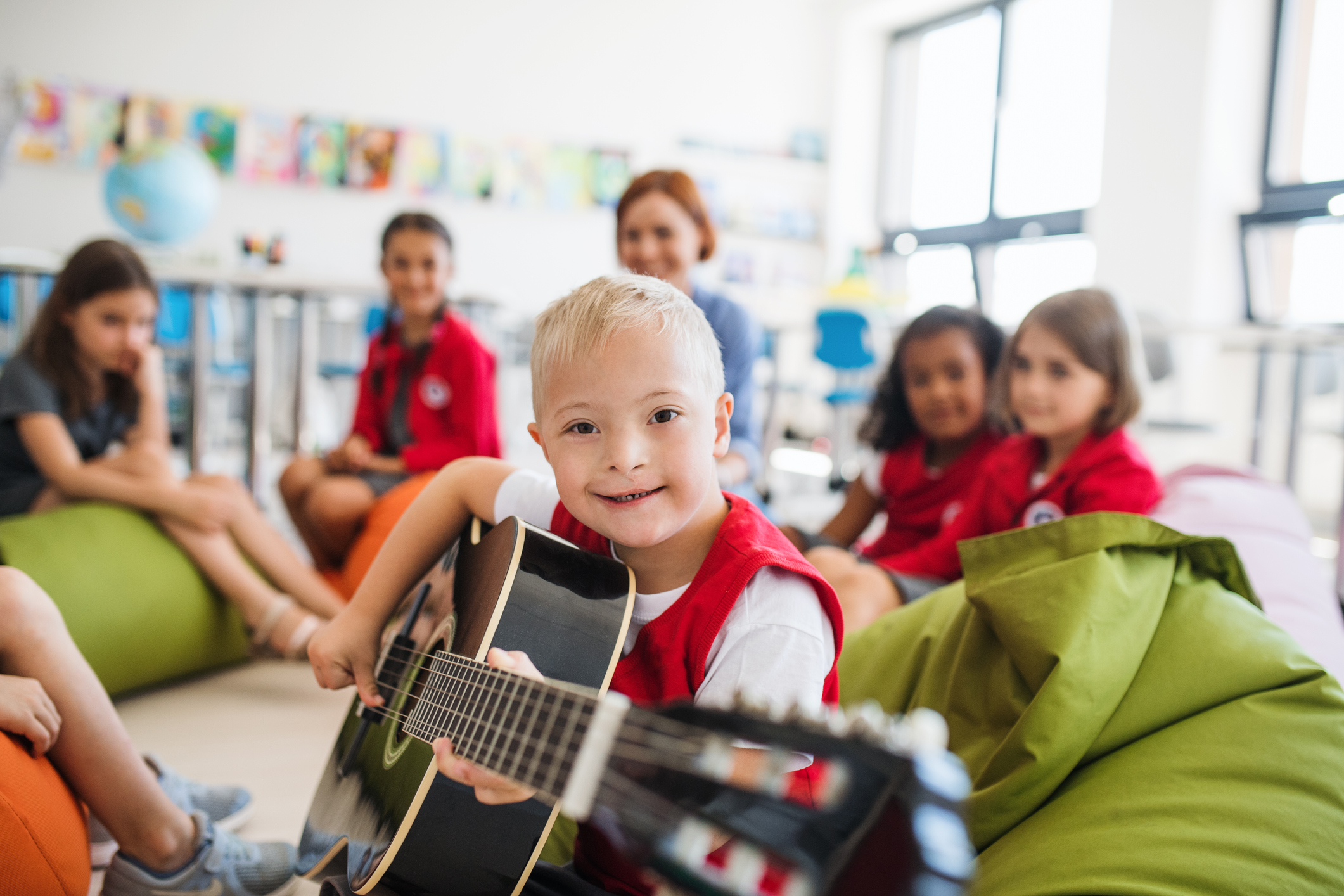 A boy with Down-syndrome playing guitar.