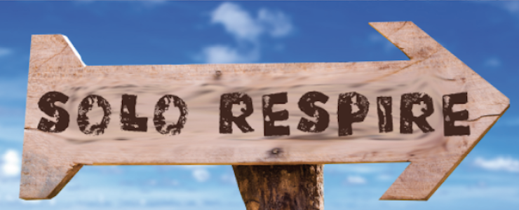 Wooden arrow sign at beach reads Solo Respire (Just Breathe)
