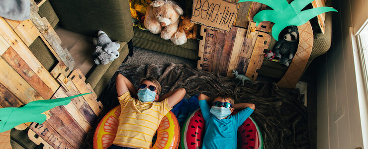 Two youth wearing masks, lying in their living room decorated as summer camp.